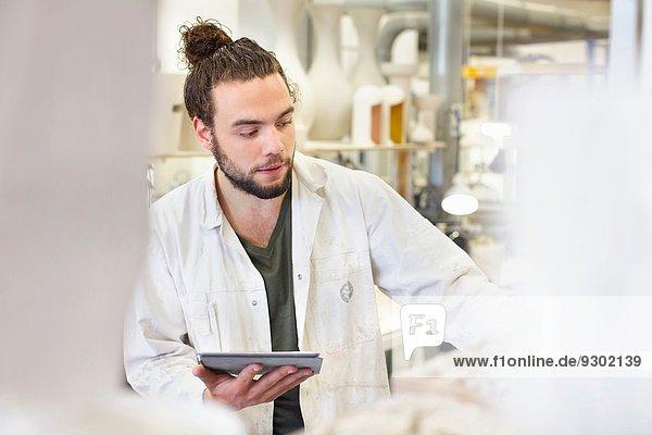 Männlicher Töpfer mit digitaler Tablette in der Keramikwerkstatt