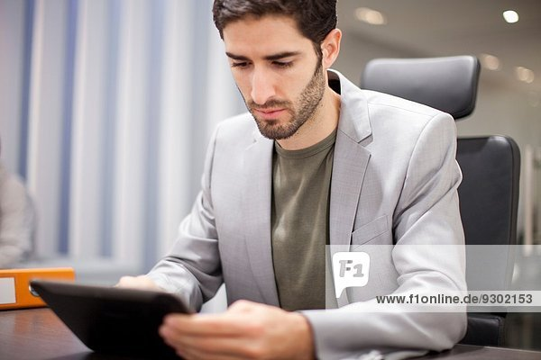 Junger Mann mit digitalem Tablett im Büro