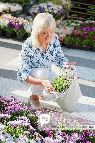 Woman with bag of flowers at market  Mallorca  Spain