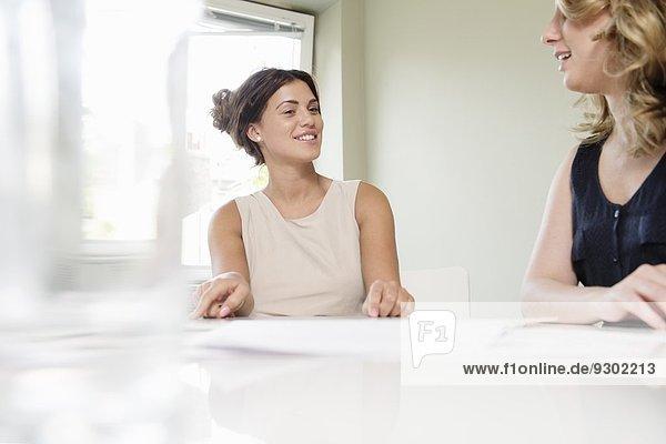 Zwei Geschäftsfrauen chatten im Konferenzraum