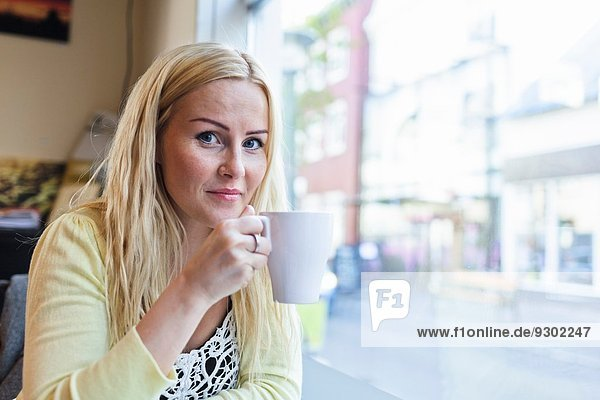 Portrait of mid adult woman drinking coffee in cafe