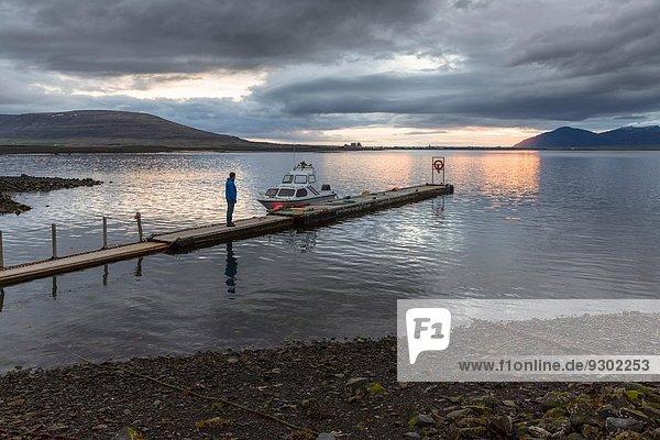 Man on pier at sunset  Hvalfjordur  Iceland