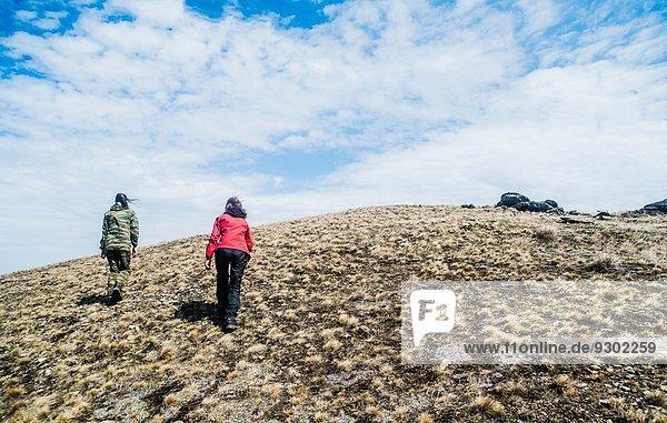 Rückansicht zweier junger Frauen beim Bergwandern