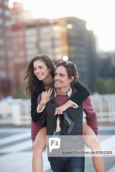 Mittlerer Erwachsener Mann gibt Freundin Huckepack in der Straße