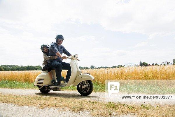 Erwachsener Mann und Tochter fahren Motorroller entlang der Schotterpiste