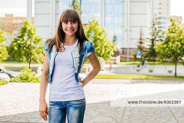 Porträt einer jungen Frau  die mit der Hand auf der Hüfte in der Stadt posiert.