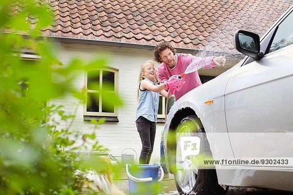 Mädchen hilft Vater beim Autowaschen