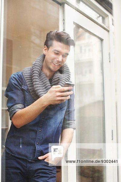 Junger Mann SMS auf Smartphone hinter Terrassenglas