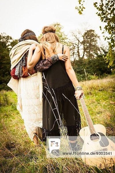 Rückansicht von Hippie-Mädchen  die mit der Gitarre durchs Feld laufen.
