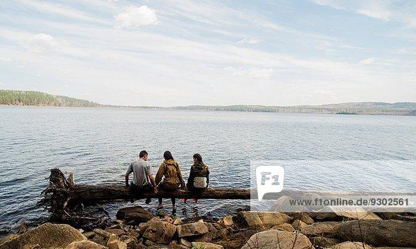 Drei Wanderfreunde sitzen in einer Reihe auf einem umgestürzten Baum am Seeufer.