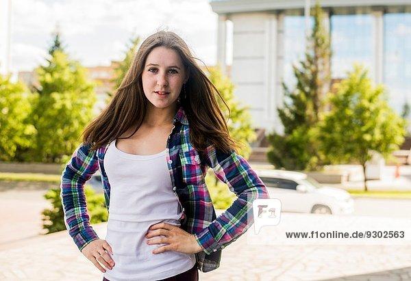 Porträt einer jungen Frau mit Händen auf den Hüften in der Stadt