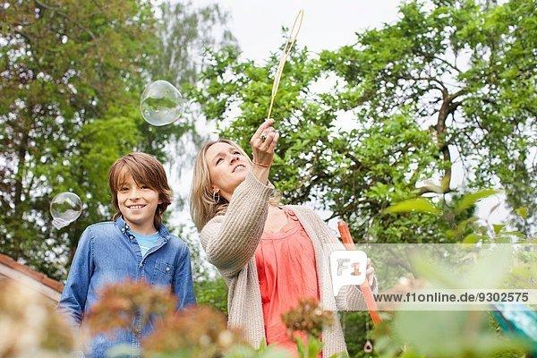 Mutter und Sohn spielen mit Seifenblasen im Garten