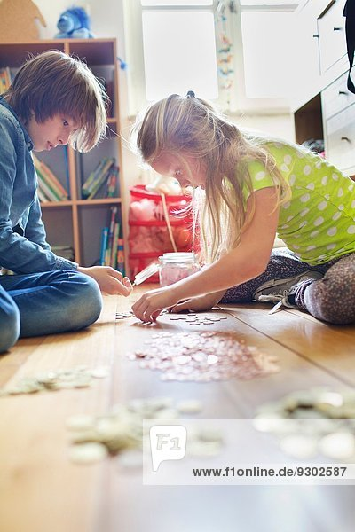 Geschwister zählen Münzen aus dem Sparglas