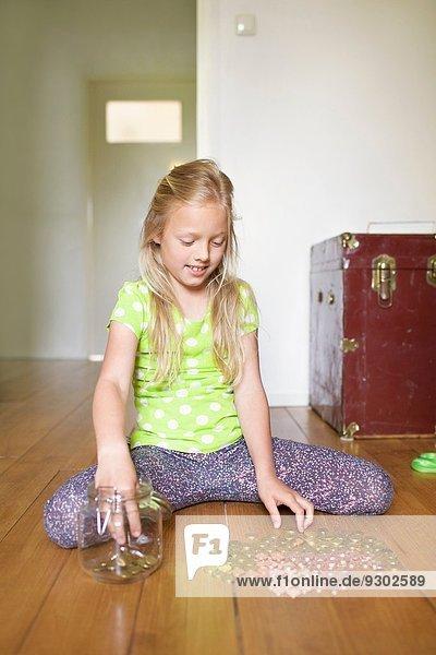 Mädchen zählen Münzen aus Sparbüchse