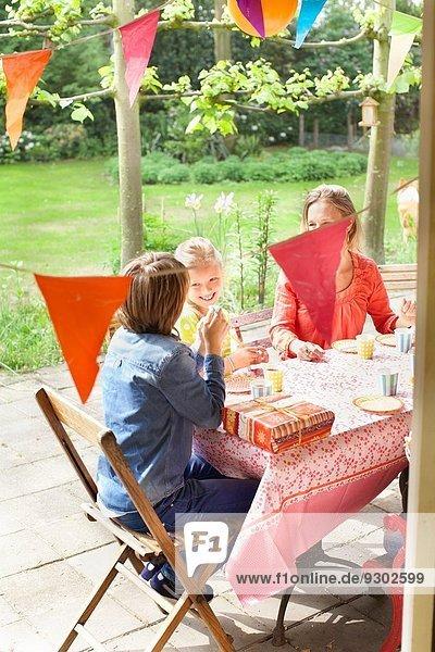 Mutter im Gespräch mit Kindern am Verandatisch