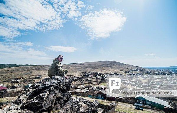 Junge Wanderin mit Blick über die Schulter auf den Berggipfel