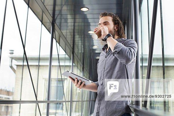 Mann mit digitalem Tablett in der Kaffeepause