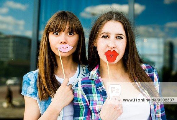 Porträt von zwei jungen Frauen  die Lippenmasken hochhalten