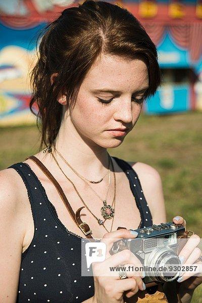 Junge Frau beim Fotografieren mit Spiegelreflexkamera auf dem Jahrmarkt