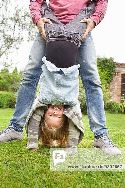 Vater hält Tochter verkehrt herum