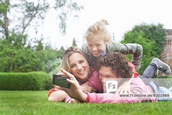 Father photographing family lying on lawn