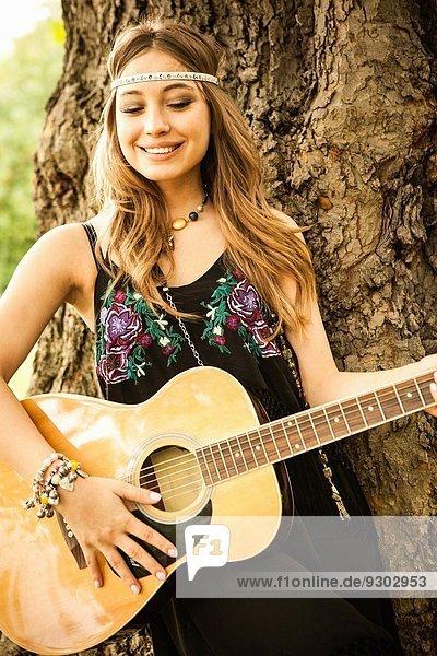 Junge Hippie-Frau beim Gitarrespielen