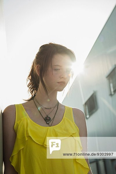 Junges mürrisches Mädchen in gelber Bluse mit Blick nach unten