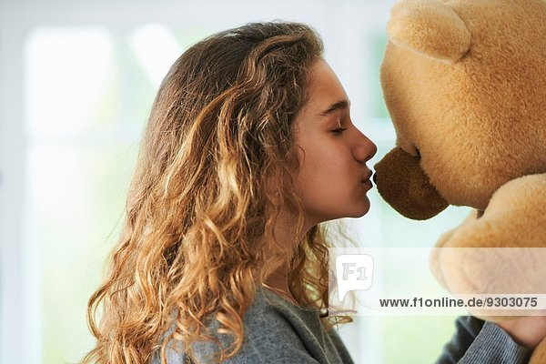 Porträt eines jungen Mädchens  das einen Teddybären küsst.