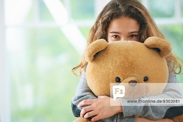 Porträt eines jungen Mädchens  das den Teddybären umarmt