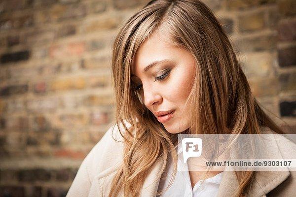 Frau mit niedergeschlagenen Augen  Backsteinmauer im Hintergrund