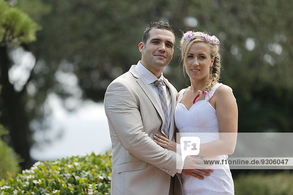 Braut und Bräutigam posieren in einem Park