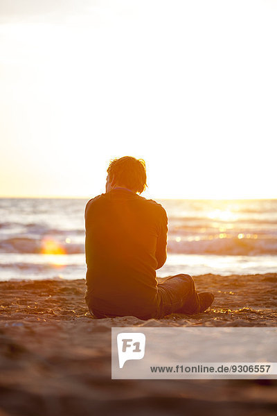 Mann sitzt am Strand  Italien  Europa