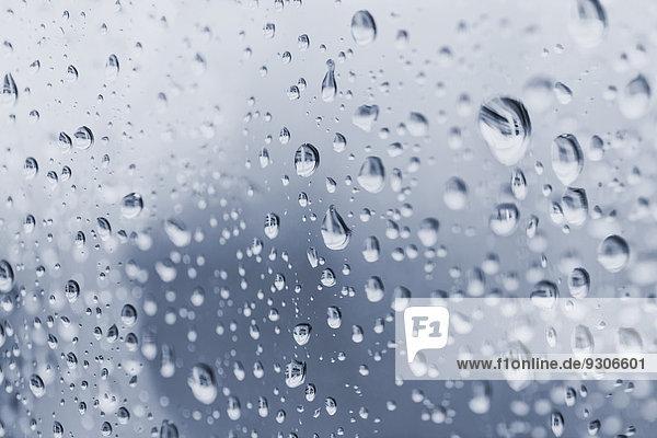 Regentropfen an einer Glasscheibe