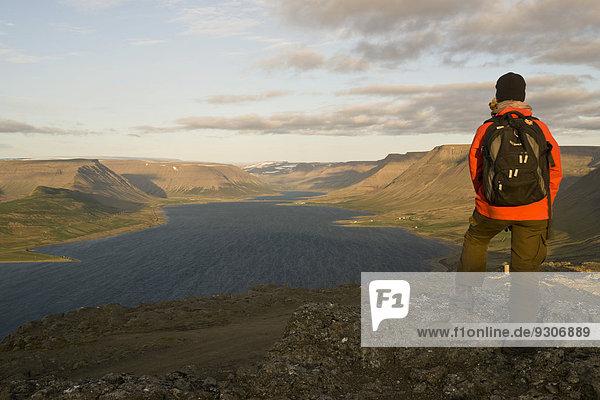 Woman looking across Dýrafjördur Fjord  Westfjords  Iceland