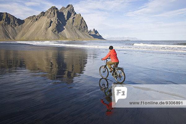 Frau fährt Fahrrad am Strand vor Berg Vestrahorn nahe Hoefn  Stokksnes  Südwesten  Island