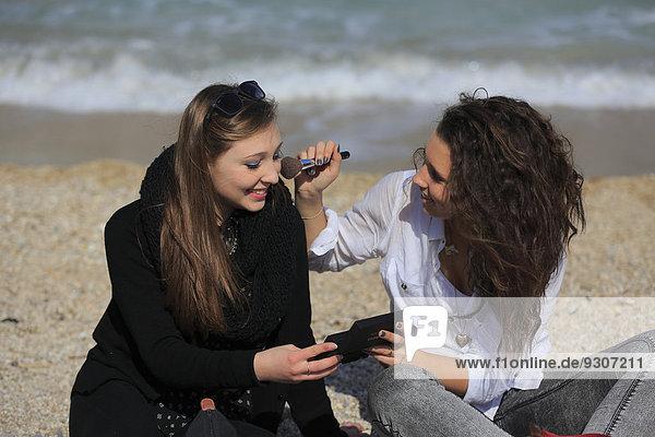 Zwei Freundinnen  Teenager  sitzen am Strand und schminken sich gegenseitig  Menton  Alpes-Maritimes  Provence-Alpes-Côte d'Azur  Frankreich