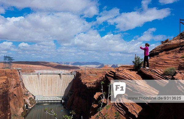 Page Arizona Glen Canyon Dam on Colorado River woman tourist taking Iphone pictures scenics with rocks and clouds for tourists West USA from above 7.