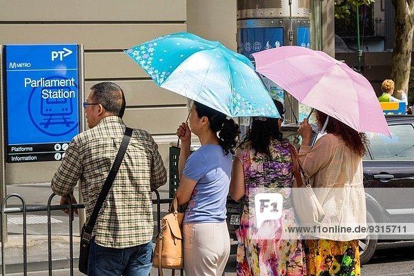 Frau Mann Regenschirm Schirm warten Zeichen Öffentlicher Verkehr Straßenbahn Victoria Metro Australien Melbourne Signal