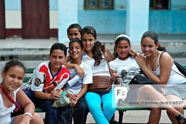 Group of Cuban children pose for a photograph on the streets of Cienfuegos.