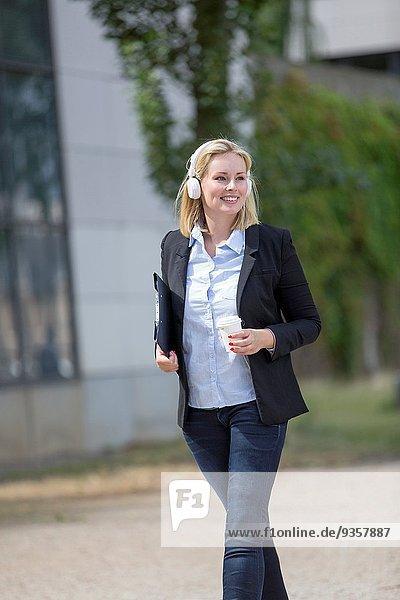 Außenaufnahme Frau gehen Kopfhörer Kaffee Chef freie Natur hübsch