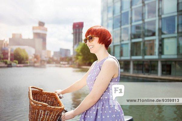 Frau schiebt Fahrrad am Kanal entlang  East London  UK