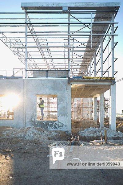 Bauleiter prüft Fensterrahmen auf der Baustelle