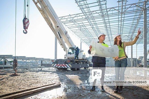 Bauleiter und Architekt prüft Bauplan auf der Baustelle