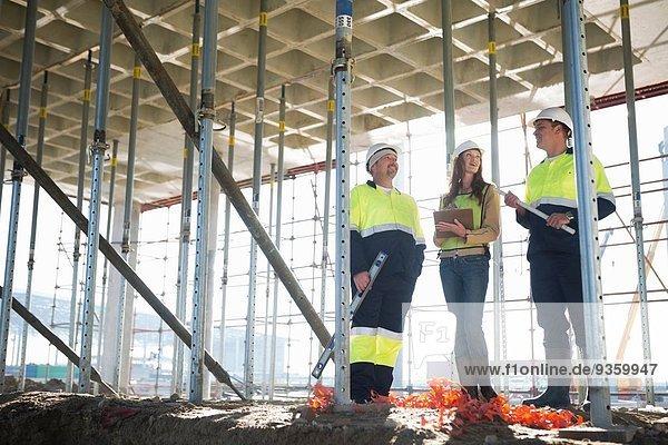 Bauleiter und Architekten im Gespräch auf der Baustelle