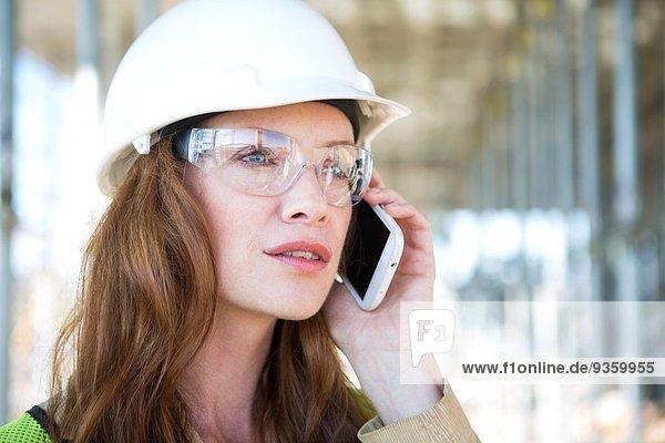 Nahaufnahme des Architektenchats auf dem Smartphone auf der Baustelle