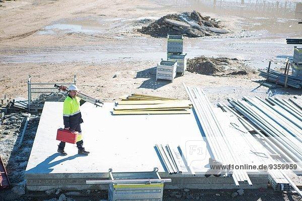 Hochwinkelansicht von Vermessungstasche und Stativ auf der Baustelle