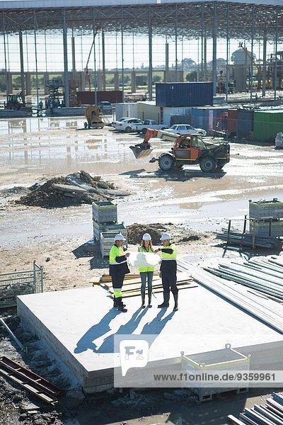 Hochwinkelansicht des Architekten und Bauleiters bei der Betrachtung des Bauplans auf der Baustelle