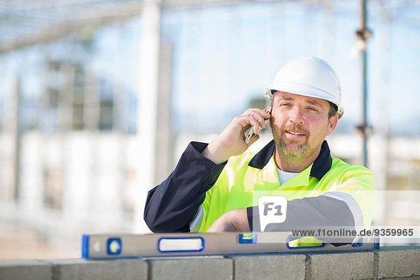 Bauherr mit Wasserwaage auf der Baustelle im Chat auf dem Smartphone
