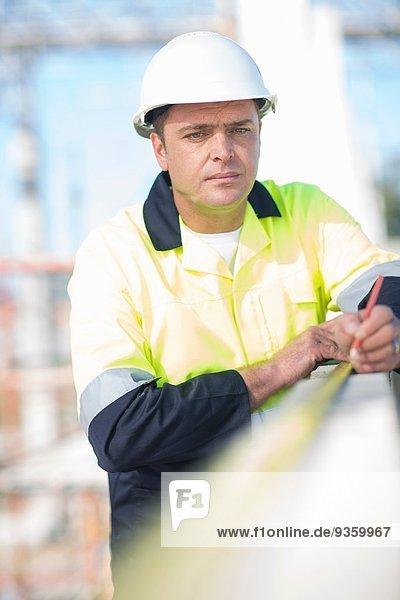 Bauherr mit Maßband an der Baustellenwand