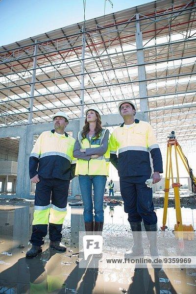 Architekten und Bauleiter beim Nachschlagen auf der Baustelle